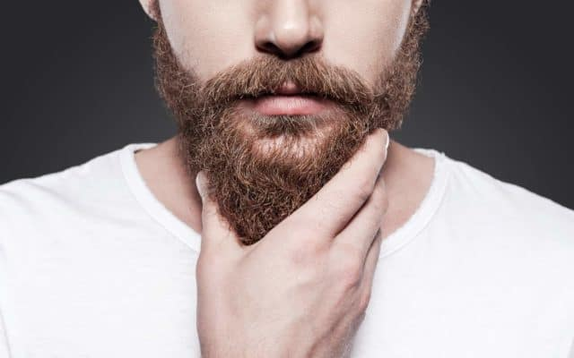 Man touches beard